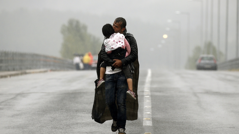 A Syrian refugee kisses his son as he walks through a rainstorm towards Greece's border with Macedonia.
