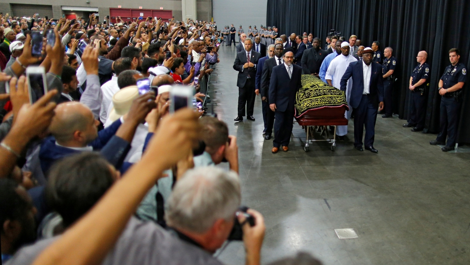 Worshipers and well-wishers take photographs as the casket with the body of the late boxing champion Muhammad Ali is brought for his jenazah, an Islamic funeral prayer, in Louisville, Kentucky, U.S. on June 9, 2016.