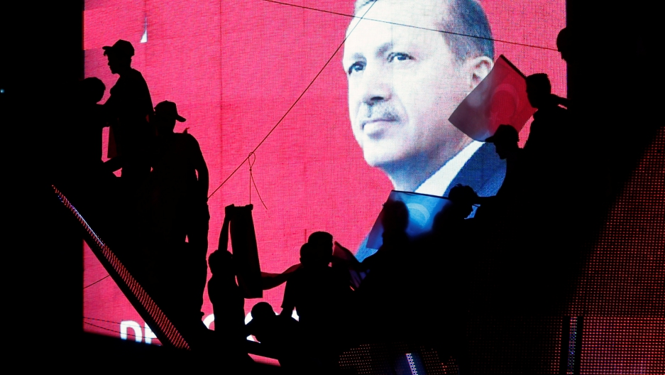 Activists in Turkey are silhouetted against a screen showing President Tayyip Erdogan during a pro-government demonstration in Ankara, Turkey, July 17, 2016.