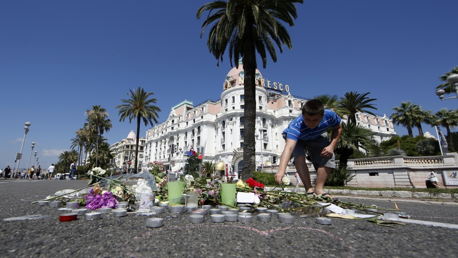 A boy places a white rose on the road in front of the Negresco hotel before a minute of silence on the third day of national mourning to pay tribute to victims of the truck attack along the Promenade des Anglais.