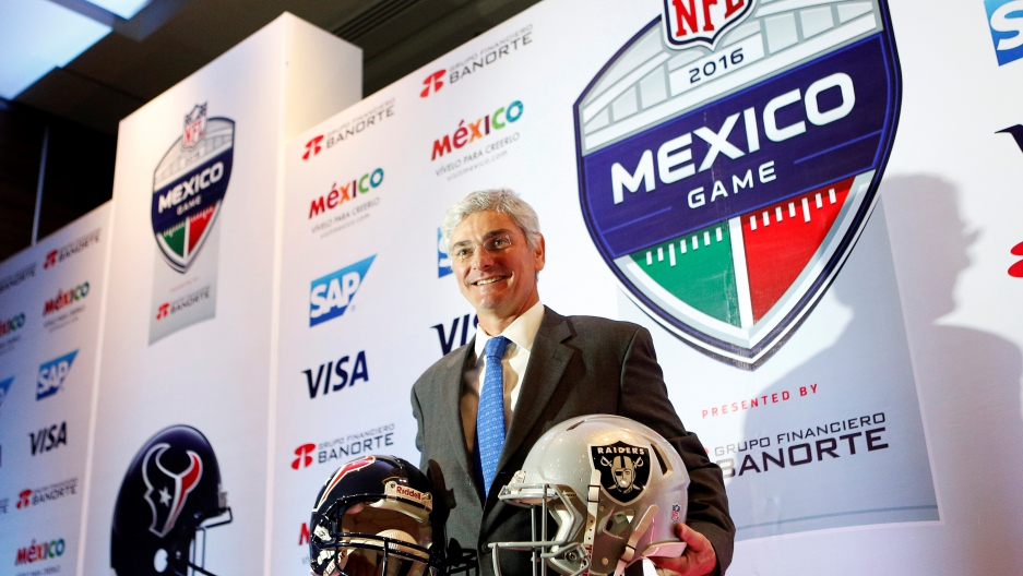 Representative of the National Football League (NFL) Arturo Oliver shows football helmets to the media to promote the regular season game between Houston Texans and Oakland Raiders, in Mexico City, Mexico July 19, 2016.