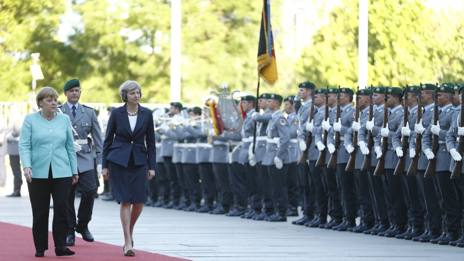 German Chancellor Angela Merkel and Britain's Prime Minister Theresa May (R) review the honour guard during a welcoming ceremony at the Chancellery in Berlin, Germany July 20, 2016.