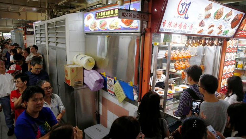 People queue outside hawker Chan Hong Meng's Michelin star awarded stall, for his soya sauce chicken rice and noodle at a food market in Singapore.