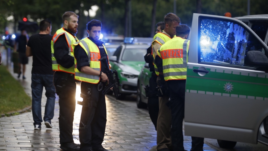 Police secure a street near to the scene of a shooting in Munich, Germany on Friday.