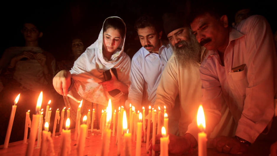 Residents light candles to honour victims of the blast in Quetta during a candellight vigil in Peshawar, Pakistan.
