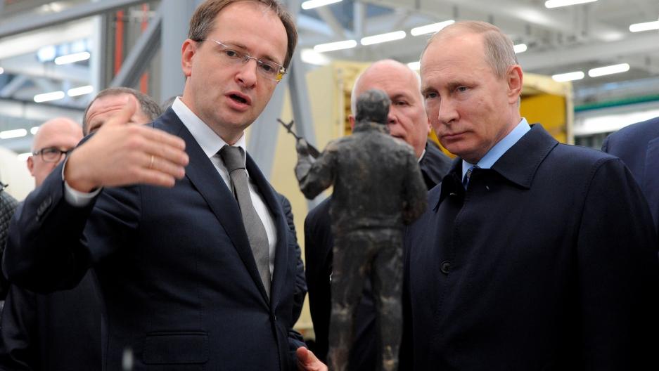 Russian President Vladimir Putin (R) listens to Culture Minister Vladimir Medinsky as they watch the project of a monument to Mikhail Kalashnikov.