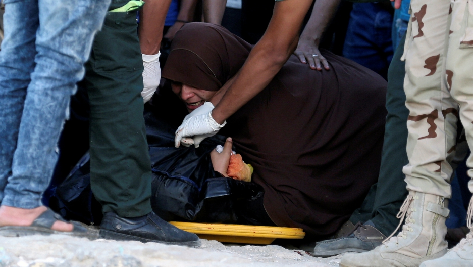 An Egyptian mother reacts beside the body of her son who was on a boat carrying migrants which capsized off Egypt's coast, in Al-Beheira, Egypt, September 22, 2016.
