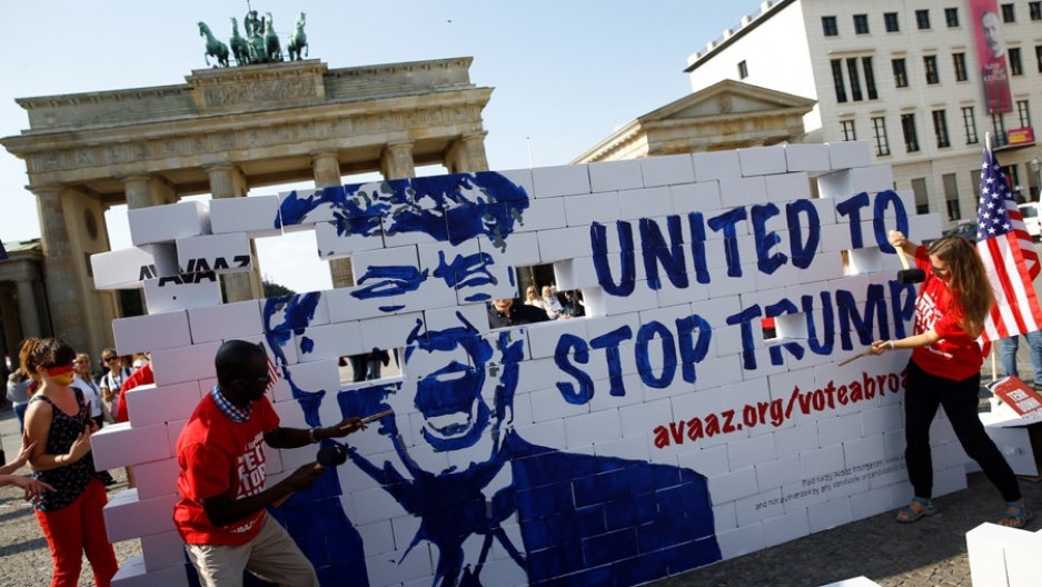 "Activists pose on a ""United To Stop Trump"" cardboard wall in front of the Brandenburg Gate in Berlin, Germany to urge Americans abroad to vote, on Sept. 23."