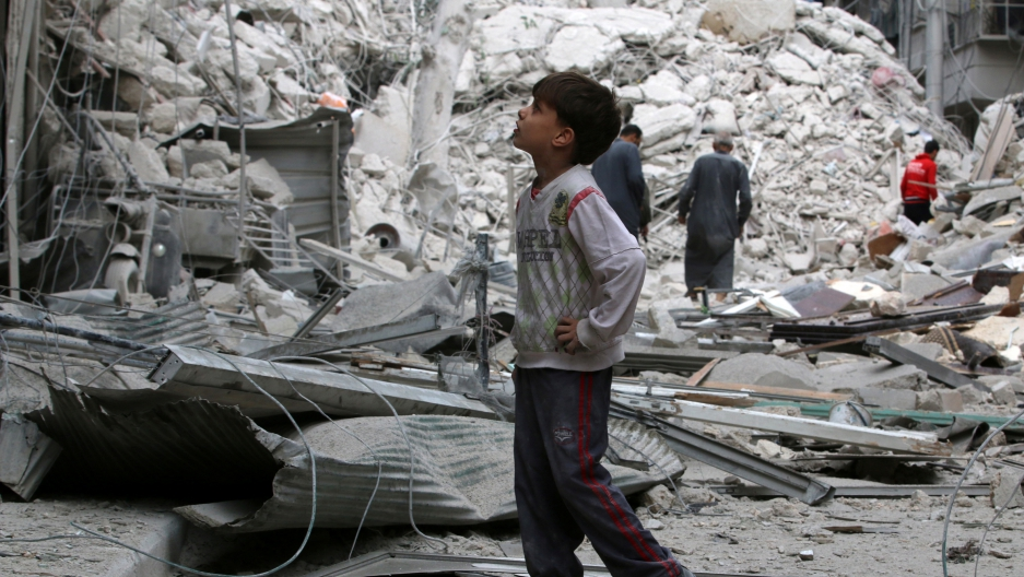 A boy inspects a damaged site after airstrikes on the rebel held Tariq al-Bab neighborhood of Aleppo, Syria September 23, 2016.