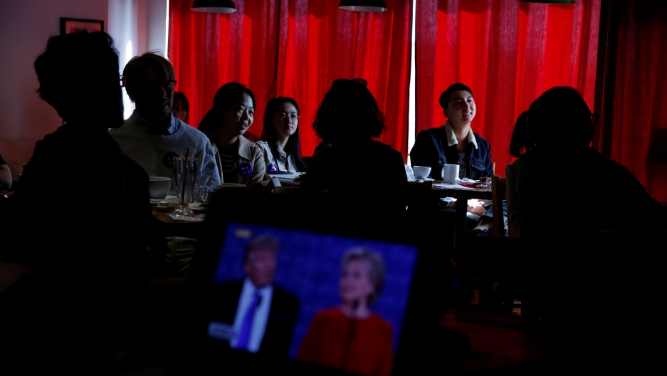 People watch a direct broadcast of the first U.S. presidential debate between Republican U.S. presidential nominee Donald Trump and Democratic U.S. presidential nominee Hillary Clinton at a cafe in Beijing, China on September 27, 2016.