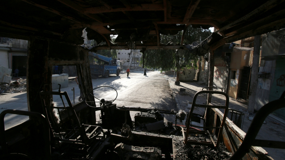 Aleppo residents walk past a burnt bus in the city's rebel-held Seif al-Dawla neighborhood.