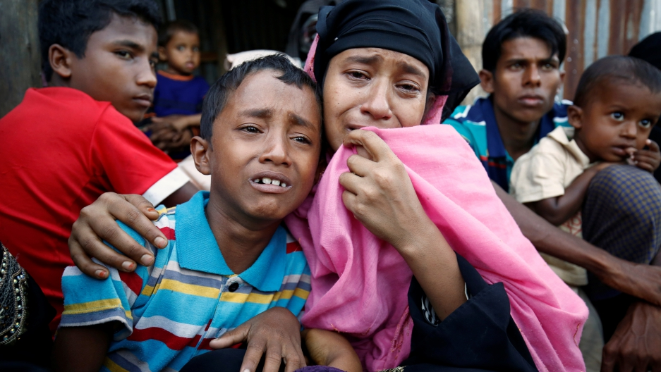 A Rohingya mother and her son weep at a border checkpoint into Bangladesh. Thousands have crossed the border to escape the violence.