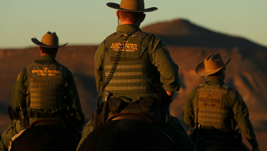 Men on horses in Border Patrol uniforms, seen from back at dusk