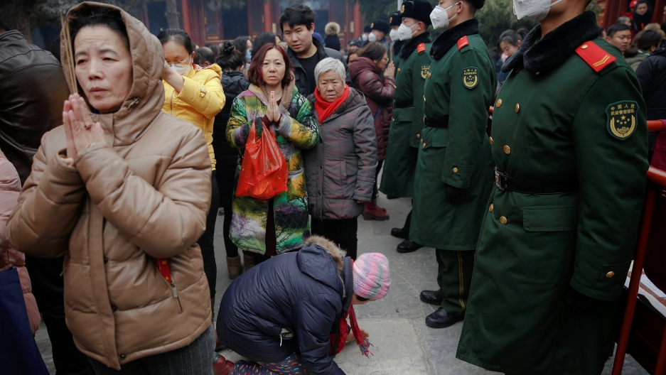 Women pray in front of paramilitary policemen at Yonghegong Lama Temple on the first day of the Lunar New Year of the Rooster in Beijing, China.