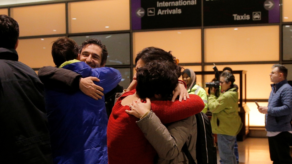 People hugging in front of airport arrival and departure signs
