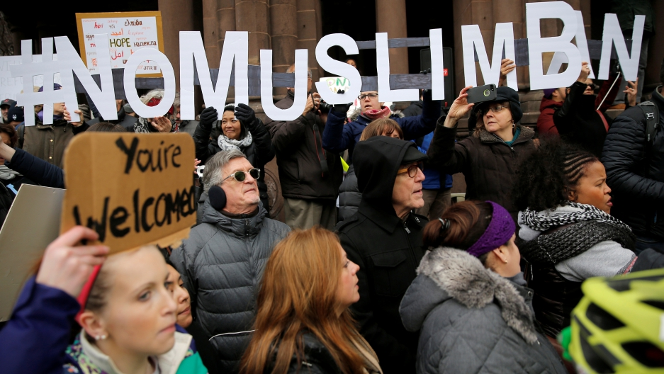 """Demonstrators spell out """"# No Muslim Ban"""" during a protest against President Donald Trump's executive order travel ban."""