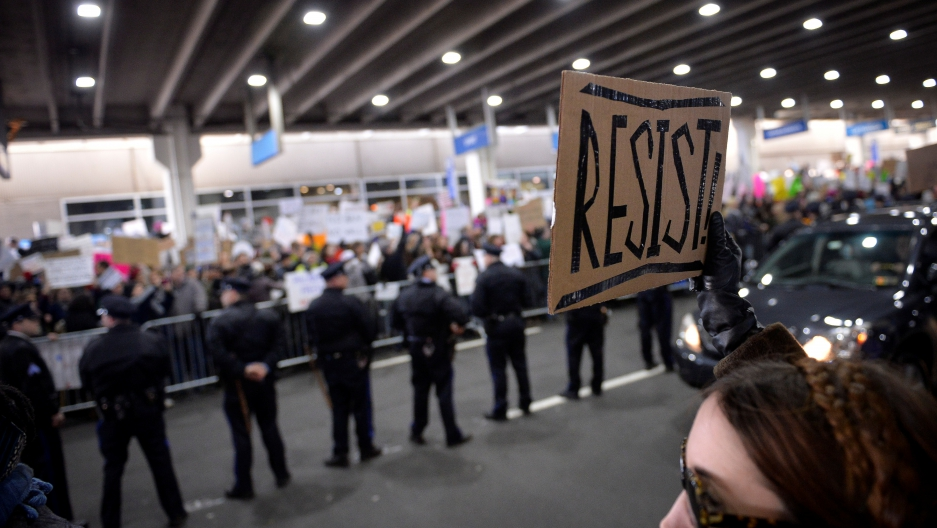 "A demonstrator holds a ""resist"" sign during anti-Donald Trump travel ban protests outside Philadelphia International Airport in Philadelphia, Pennsylvania, U.S., January 29, 2017."