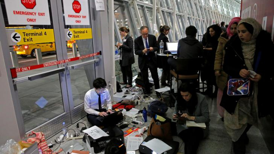 ​Women walk by a team of volunteer lawyers in their makeshift office working to assist travelers detained as part of Donald Trump's travel ban in Terminal 4 at John F. Kennedy International Airport in Queens.