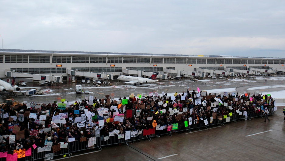 Protesters at airport, protesting outdoors in front of airplanes