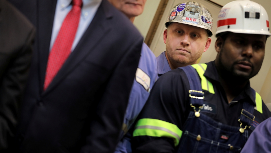 Two coal miners stand in the white house.