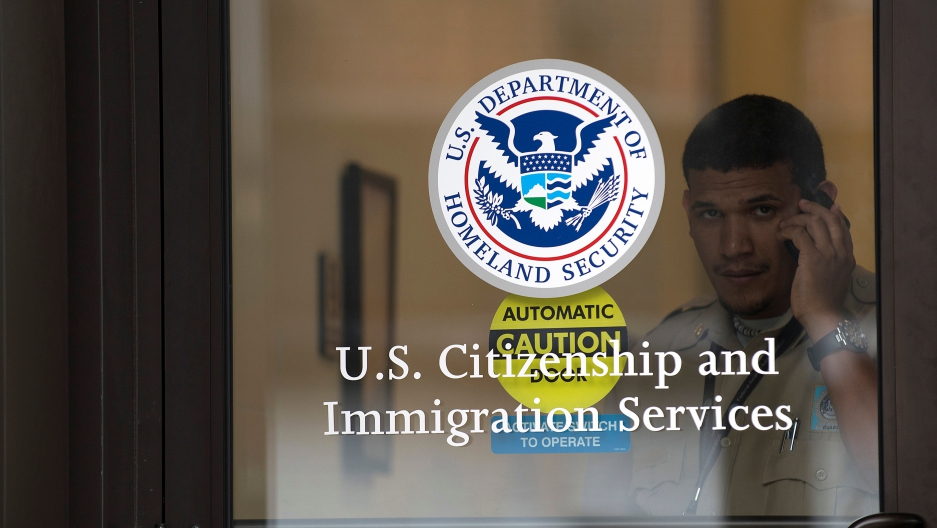 A security guard looks out of the U.S. Citizenship and Immigration Services offices in New York, U.S. on August 15, 2012.
