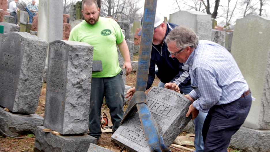 Spencer Pensoneau, Ron Klump and Philip Weiss (left to right), of Weiss and Rosenbloom Monument company, work to right toppled Jewish headstones after a weekend vandalism attack on Chesed Shel Emeth Cemetery in University City, a suburb of St Louis, Misso