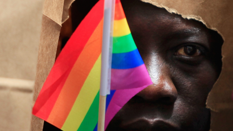 An asylum-seeker from Uganda covers his face with a paper bag in order to protect his identity as he marches with the LGBT Asylum Support Task Force during the Gay Pride Parade in Boston, Massachusetts, June 8, 2013.