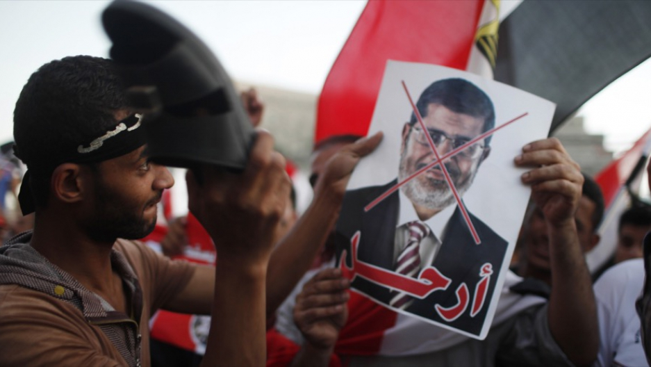 A protester uses his sandal to beat a picture of Egypt's then-President Mohammed Morsi in Tahrir square in Cairo on June 28, 2013.
