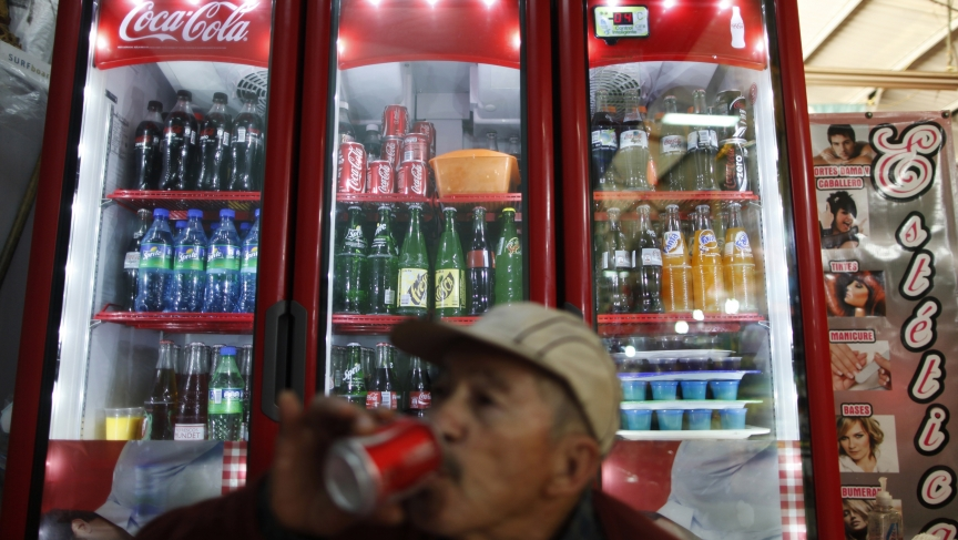 A man drinks a soft drink at a store in Mexico City. Last year, the Mexican government has imposed a 1 peso per liter tax on soda and sugary drinks to combat obesity.