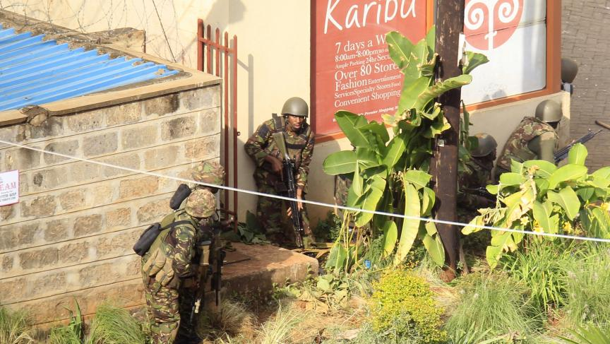 Kenyan soldiers take cover behind walls near the Westgate shopping centre after an exchange of gunfire inside the Westgate mall in Nairobi, Monday.