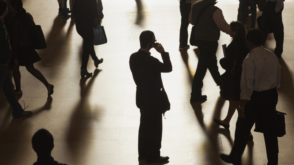 A man stands in the middle of Grand Central Terminal as he speaks on a cell phone.