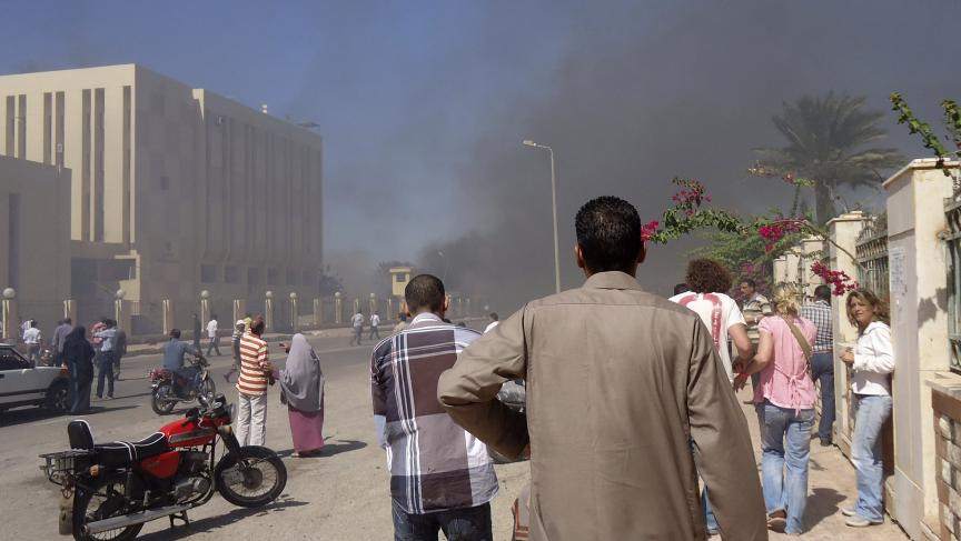 Residents and tourists watch as smoke rises from a state security building in the Sinai after a car bomb blast. Medical sources said three were killed and 48 injured in the attack.