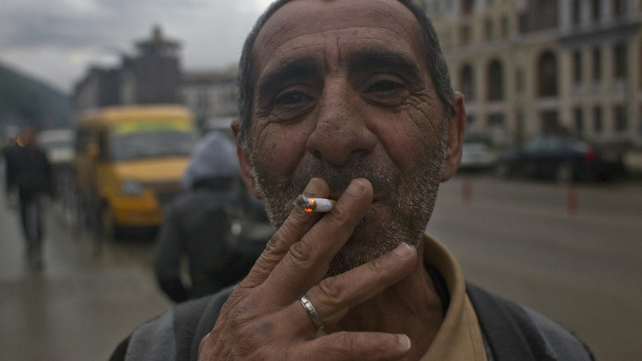 A migrant worker smokes in the village of Krasnaya Polyana, a venue for the Sochi 2014 winter Olympics, some 40 kilometres (25 miles) east from Sochi September 21, 2013.