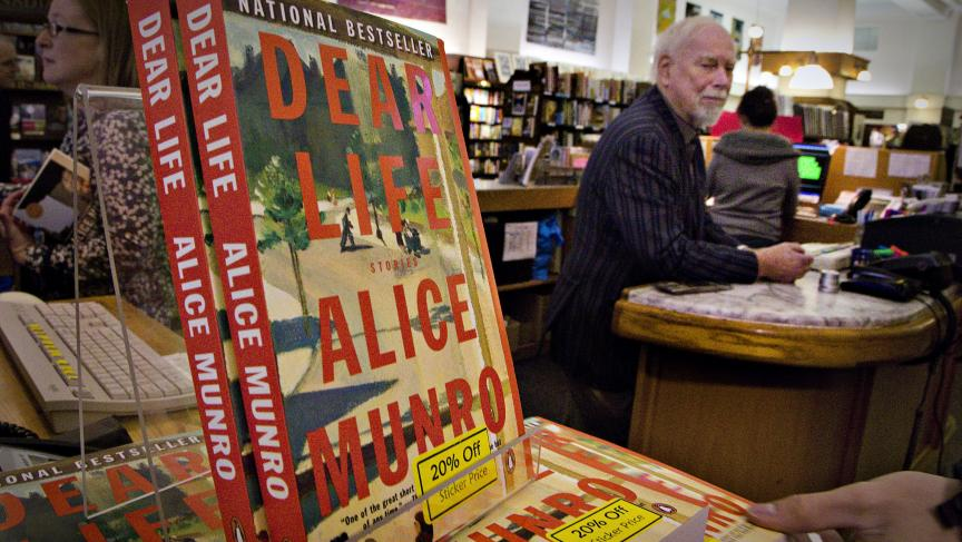 Canadian author Alice Munro's books sit on the bookshelf as her former husband Jim stands at the front counter at Munro's Bookstore in Victoria, British Columbia October 10, 2013.