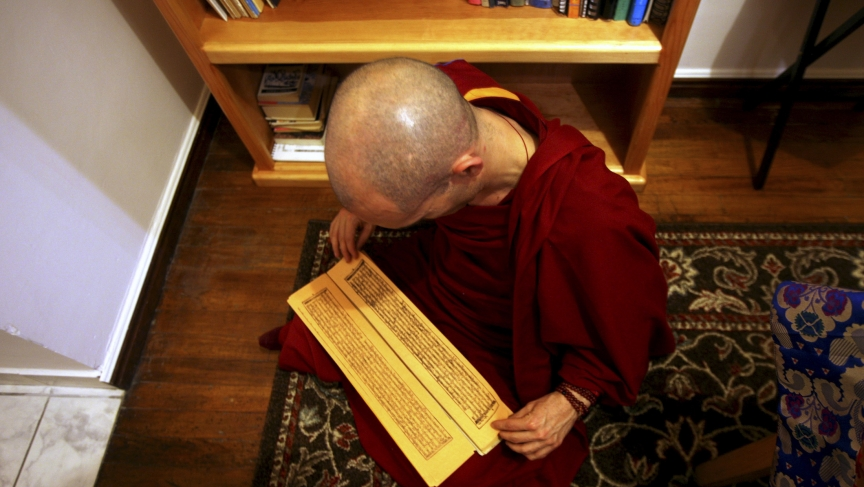 A Tibetan Buddhist monk reads from a traditional Tibetan book sitting in his lap.