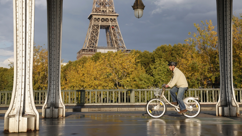 A man rides a Velib self-service public bicycle under an elevated metro line near the the Eiffel Tower after a brief rain shower in Paris October 26, 2013.