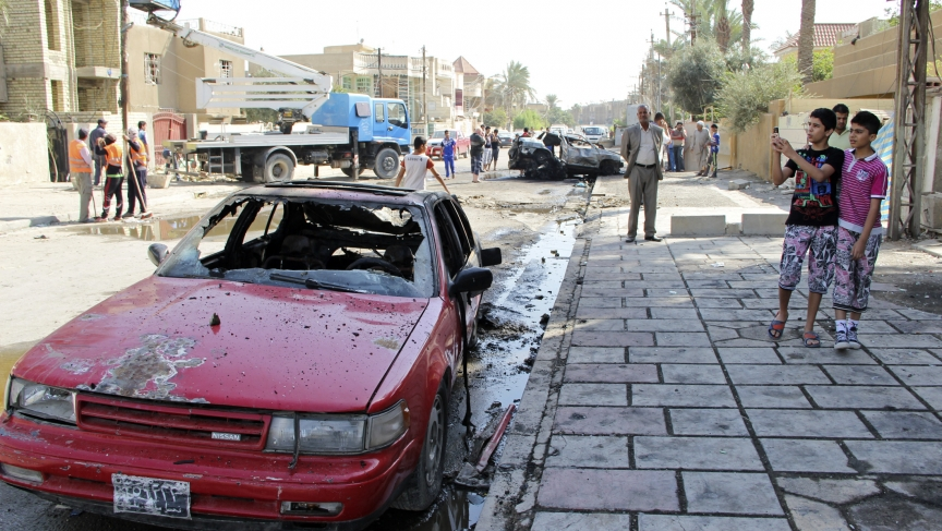A youth takes pictures with his mobile phone at the site of a car bomb attack in Baghdad, Tuesday. Violence is on the rise in Iraq, but Iraqis also face serious public health issues.