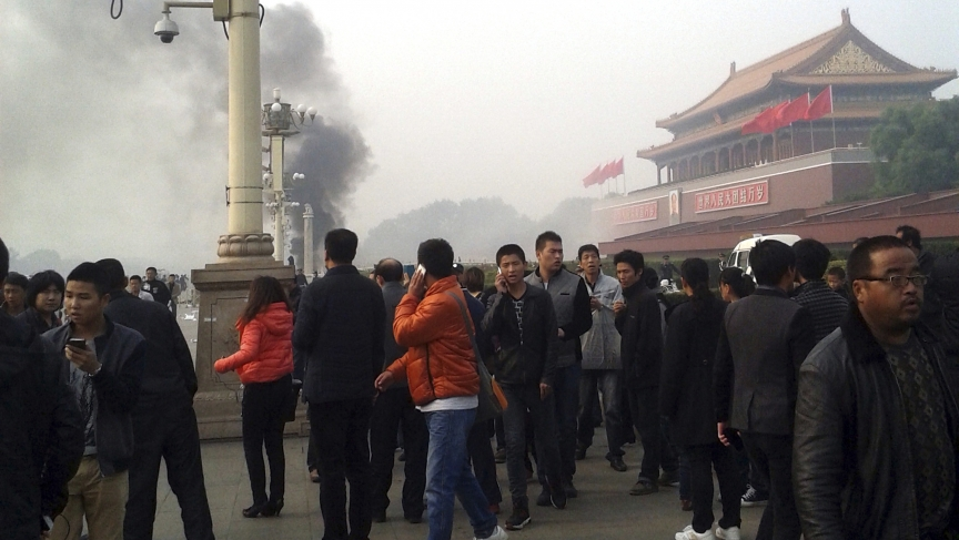 People walk along the sidewalk of Chang'an Avenue as smoke raises in front of the main entrance of the Forbidden City at Tiananmen Square in Beijing, on October 28, 2013.