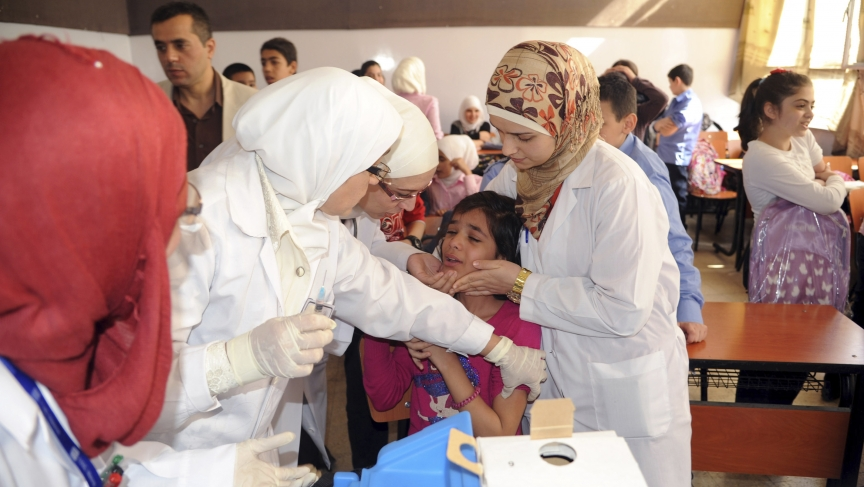 Syrian health workers administer polio vaccination to a girl at a school in Damascus, in this file photo taken by Syria's national news agency SANA in October.