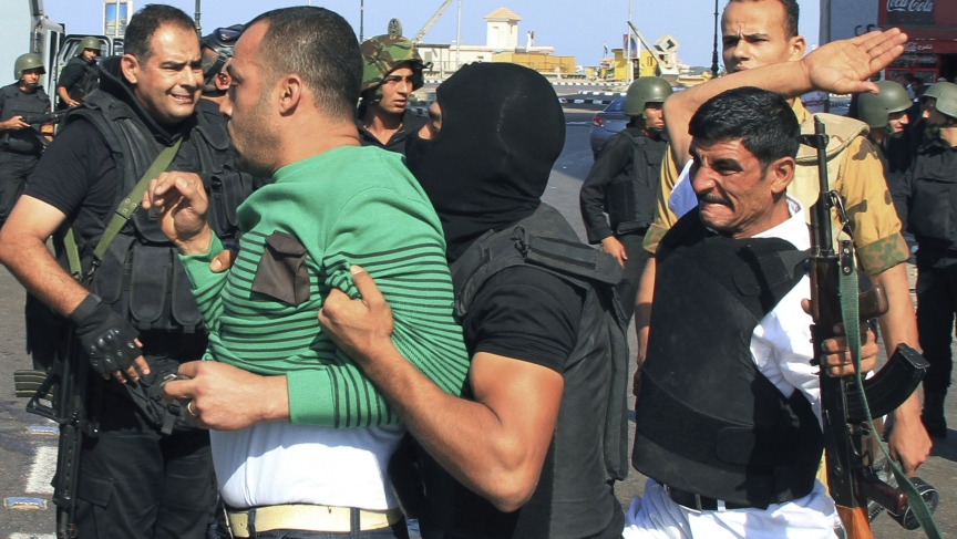 Security forces arrest a pro-Mursi protester during clashes
