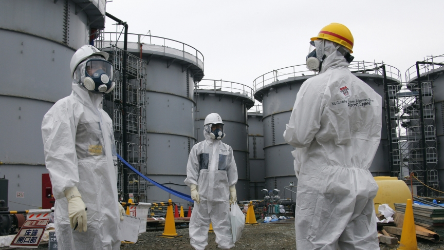 A Tokyo Electric Power Corp (TEPCO) official and journalists wearing protective equipment stand near storage tanks for radioactive water at Japan's tsunami-crippled Fukushima Daiichi nuclear power plant in November, 2013. A team of Japanese scientists say