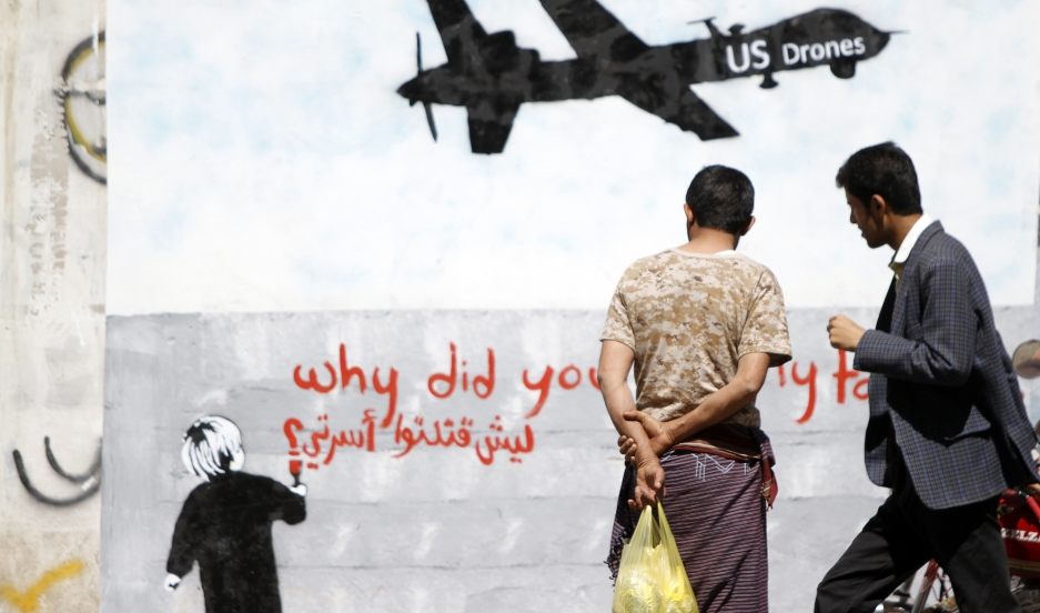 Men look at wall graffiti depicting a American drone along a street in Sana'a, Yemen, on November 9, 2013.