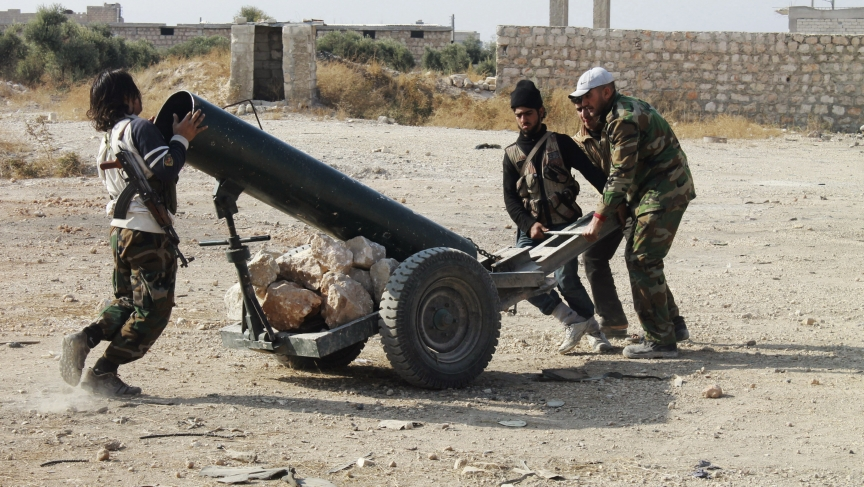 Free Syrian Army fighters prepare a locally-made launcher beside Aleppo International Airport.