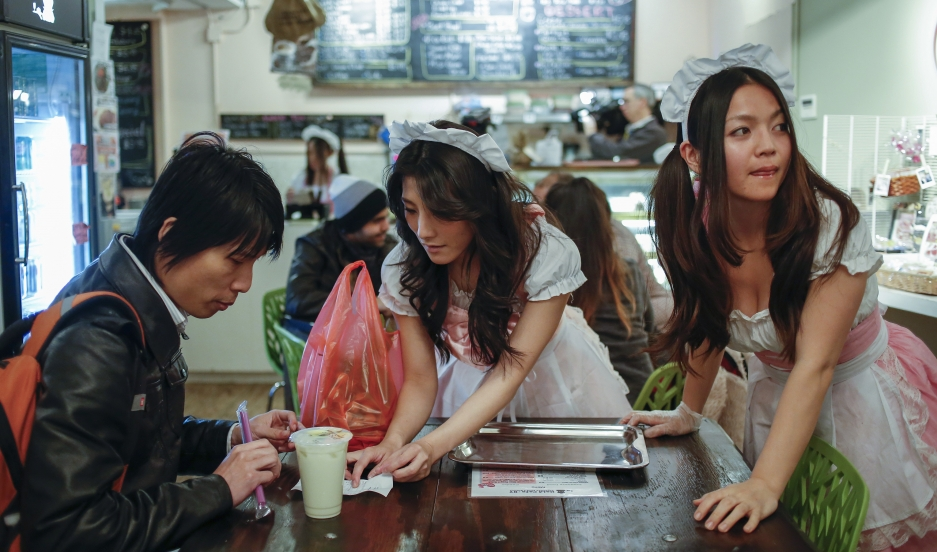Waitresses at the Maid Cafe New York serve an order at the cafe on November 20, 2013. Such cafes have existed in Japan for years, designed to cater to the fantasies of anime and manga fans.
