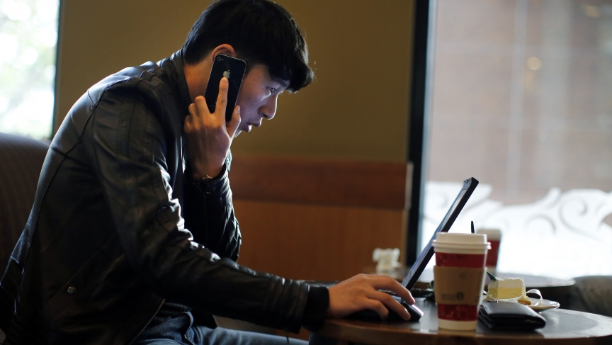 A man talks on the phone as he surfs the internet on his laptop at a local coffee shop in downtown Shanghai.