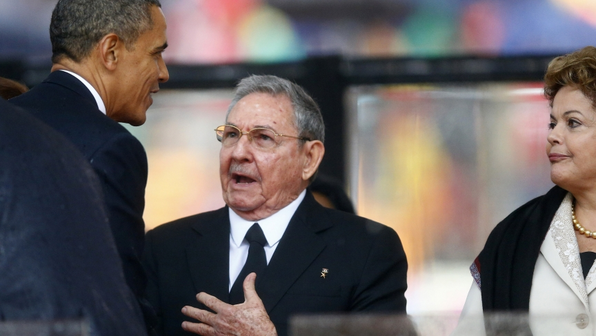 U.S. President Barack Obama greets Cuban President Raul Castro before giving his speech, as Brazil's President Dilma Rousseff looks on, at the memorial service for late South African President Nelson Mandela