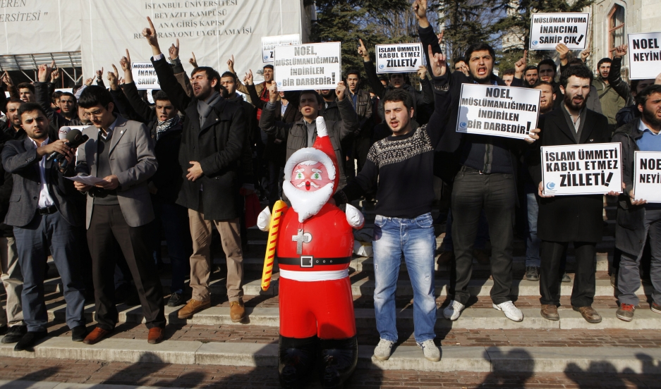"""Turkish Islamist protesters shout slogans against Noel celebrations as they hold an inflatable Santa Claus toy during a demonstration at Beyazit Square in Istanbul December 26, 2013. The sign (front, 2nd) reads: """"Christmas is a blow to our Islamism""""."""