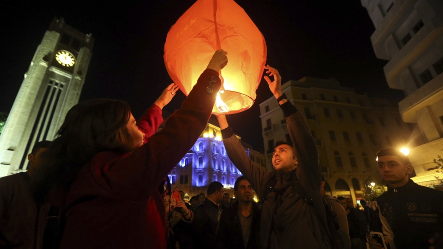 Beirut residents light a lantern during New Year's celebrations at Star Square