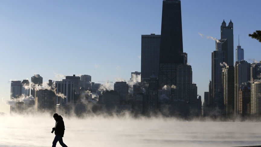 A man is silhouetted against condensation rising off of Lake Michigan in Chicago on January 6, 2014. Chicago was experiencing historic cold this week.