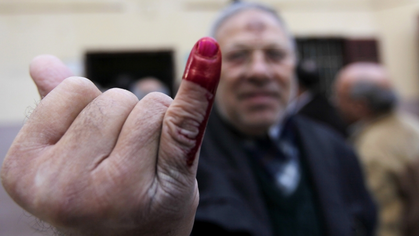An Egyptian man shows his ink-stained finger after voting in Cairo in the referendum on a new constitution.